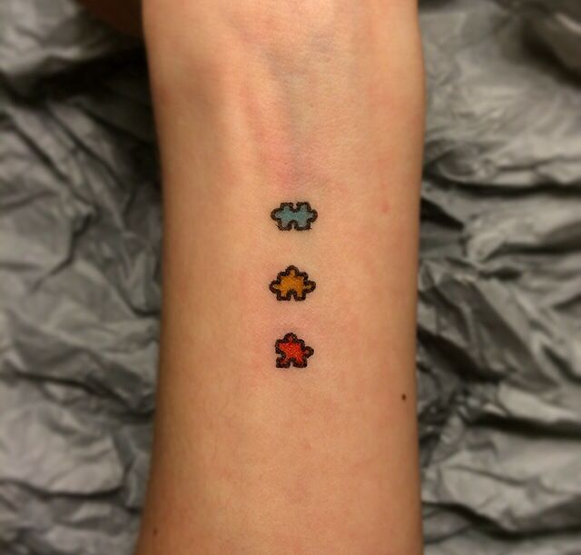 autism puzzle tattoo forearm